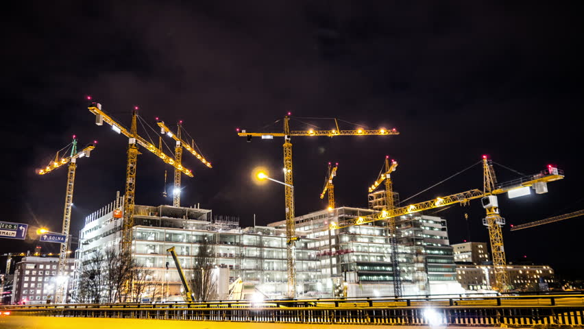 Construction site at night Time Lapse. Working tower cranes, buildings and traffic
