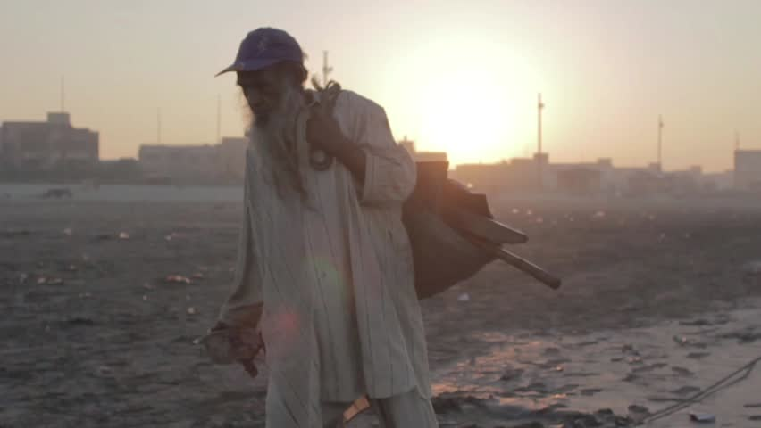 An old poor man collecting garbage at the beach at sunrise in slow motion at Sea view, Karachi, Pakistan, 26th September 2012 | Shutterstock HD Video #23432035