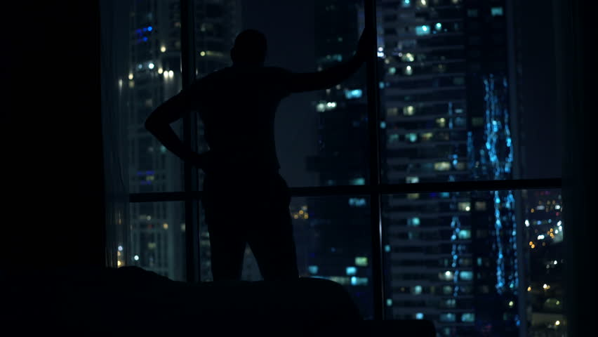 Silhouette of man having problems with sleep, waking up and standing by window at night  | Shutterstock HD Video #23436418