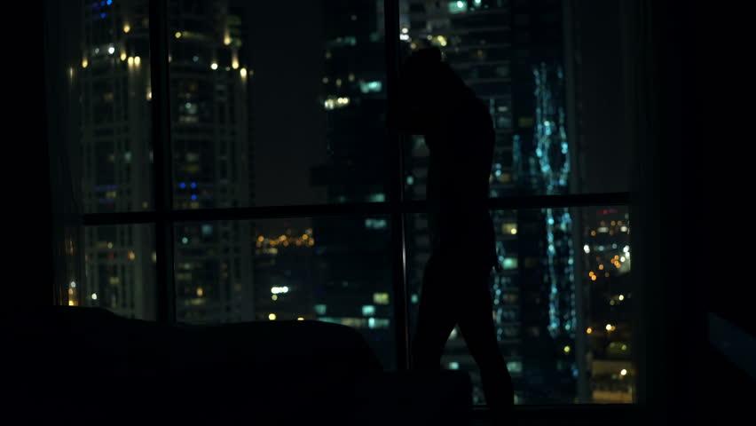 Silhouette of pensive woman walking in bedroom by window at home  | Shutterstock HD Video #23436550