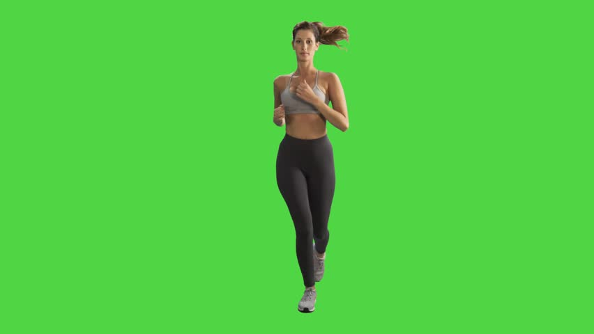 Young woman running while looking into the camera and smiles, wearing a sport bra over green screen
