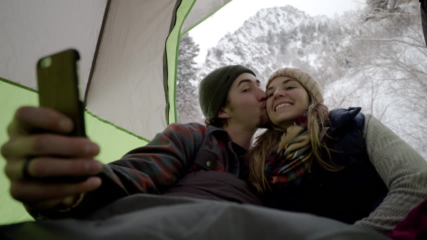 Cute Couple Take Fun Selfies Together From Their Tent, Then They Scroll Through And Laugh At Them, Snowy Mountain Peak In Background   Shutterstock HD Video #23448895