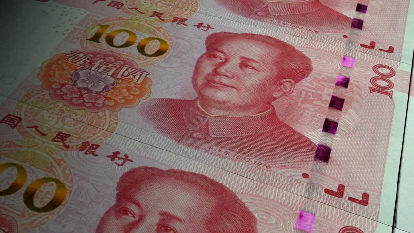 China Yuan banknotes emerging from the money press