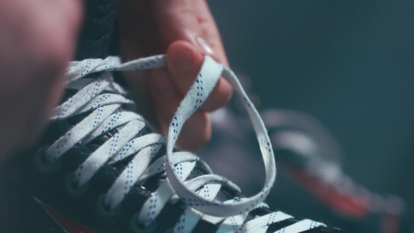 EXTREME CU Caucasian ice hockey player tightening laces on his skates in the locker room, preparing for the game. 4K UHD 60 FPS RAW edited footage #23454109