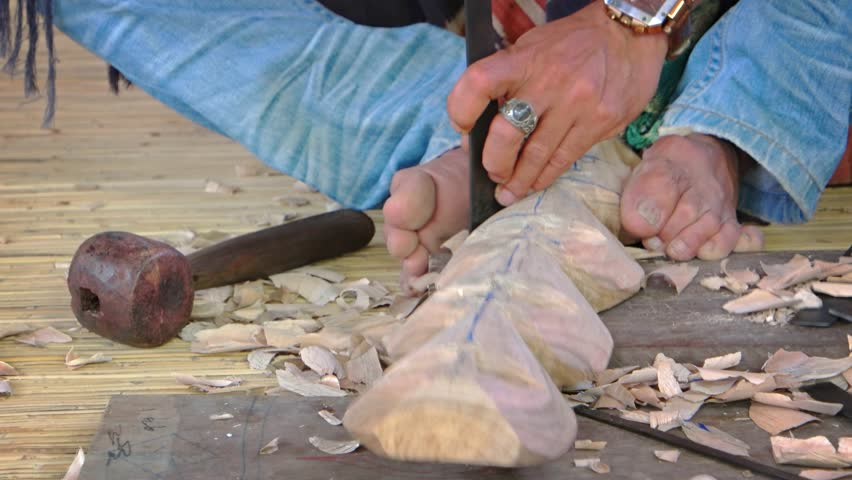 Local artists holds a wooden blank with his feet while carving away pieces with traditional hand tools in Indonesia.   Shutterstock HD Video #23456743