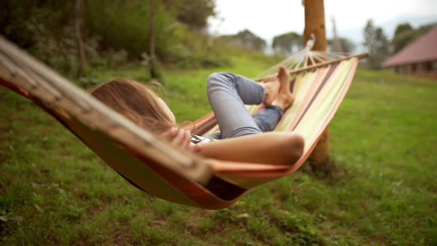 Young Caucasian female resting lying on hammock among two poles outdoors in slowmotion #23459506