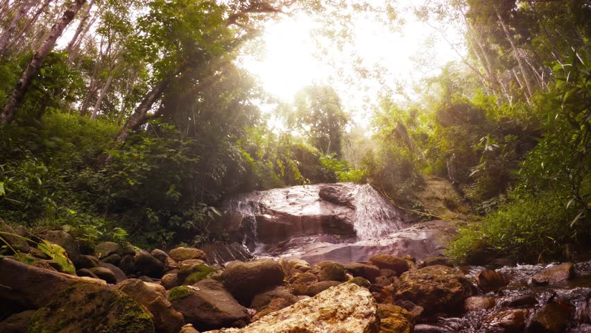 Psychedelic natural landscape. Tropical rainforest. waterfall and rays of sun. UltraHD 2160p 4k video