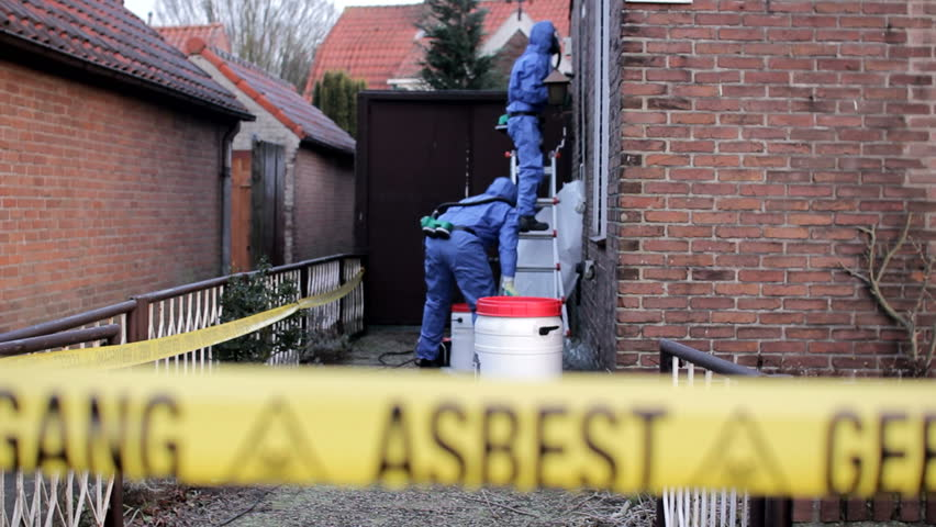 Asbestos Removal team in blue protection overalls behind yellow warning tape in Holland