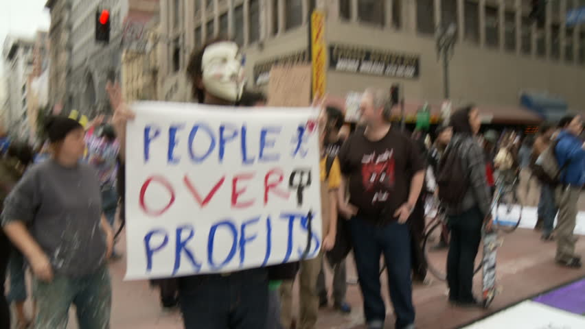 """Occupy Protester 'Vendetta' Mask. Protester wears a 'vendetta' mask and holds a sign that reads: """"PEOPLE OVER PROFITS"""" at an Occupy Rally in downtown Los Angeles, California on May 1st, 2012."""