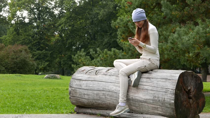 Young adult woman sit resting alone in park, stare to smartphone. Hipster girl ensconce lop down on large log, texting on mobile phone. Green lawn and bushes on background. Relaxed lady dangle on feet | Shutterstock HD Video #23479714