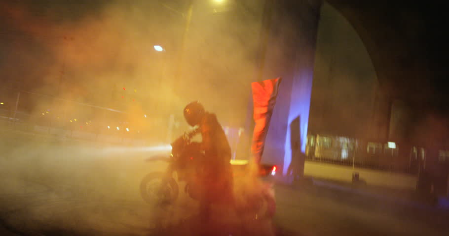 A dirt bike does donuts downtown at night its light flaring at the camera, then drives off | Shutterstock HD Video #23480692