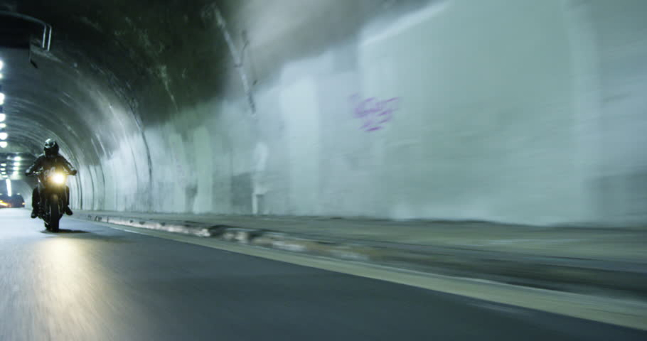 Tracking shot of a motorcycle speeding through a tunnel at night | Shutterstock HD Video #23480710