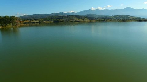 A great lake in the mountains. The water reflects. AERIAL About reflection, autumn, mountains, hill, nature, panorama