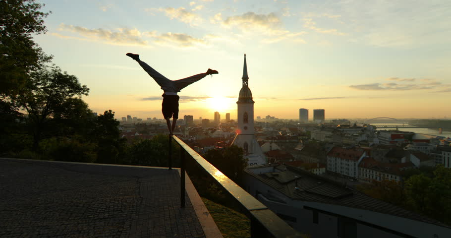 Young Man Doing Handstand on the Rail During Sunrise