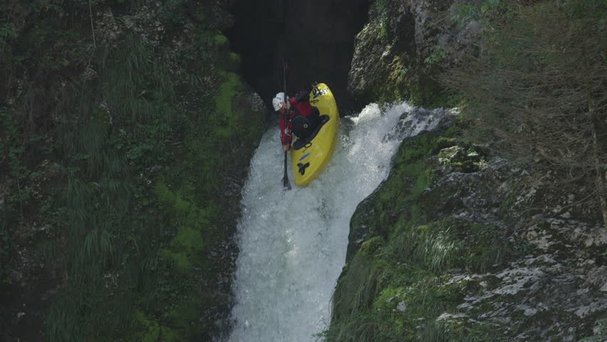 SLOW MOTION, CLOSE UP: Extreme pro canoer soaring above raging whitewater river washing rocky mountain ledge. Adrenaline rushing through man descending on the rapids and paddling through big waterfall | Shutterstock HD Video #23559721
