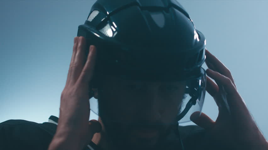 CU Portrait of Caucasian male ice hockey player in black uniform putting on his protective helmet in locker room, turning into camera. 4K UHD 60 FPS slow motion. RAW edited footage