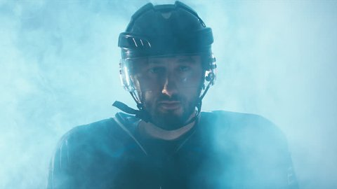 CINEMAGRAPH - seamless loop. CU Portrait of Caucasian male ice hockey player in black uniform, looking into the camera. 4K UHD