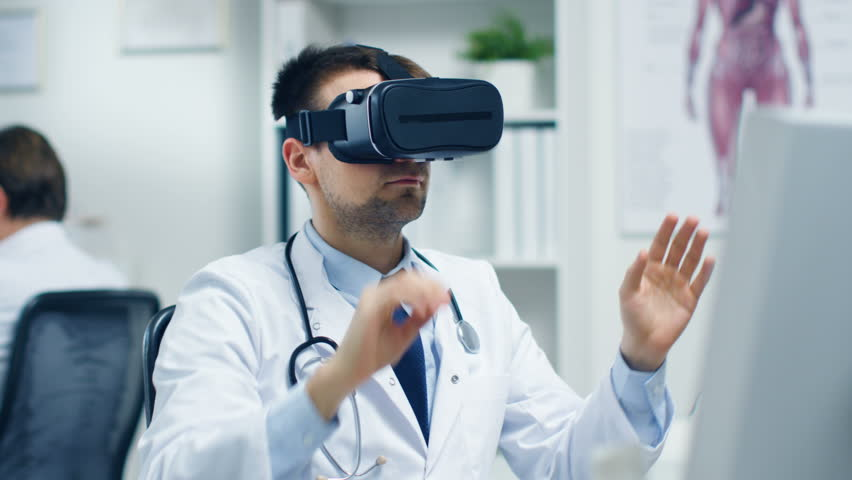 Male Doctor Conducting Experimental Medical Procedure Wearing Virtual Reality Headset. His Assistant Closely Monitors Activity from His Desk.Office is Light and Ultra-Modern. Shot on RED Cinema Camera | Shutterstock HD Video #23570935