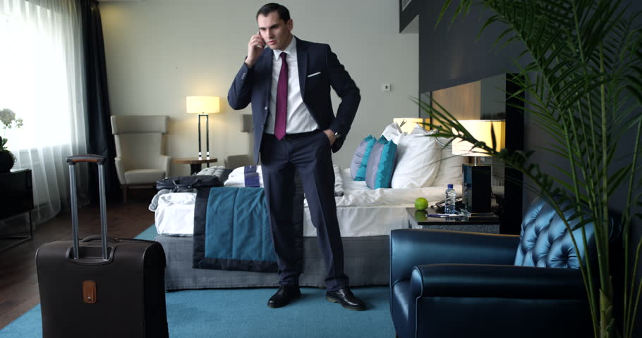 Businessman is having an unpleasant conversation on his phone straight after arriving in hotel room. We can say that he looks angry, but tries to keep calm/Unpleasant Conversation in a Hotel Room | Shutterstock HD Video #23571658