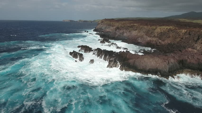 Aerial shot of ocean waves crashing coastline cliff, steep - Socorro Island