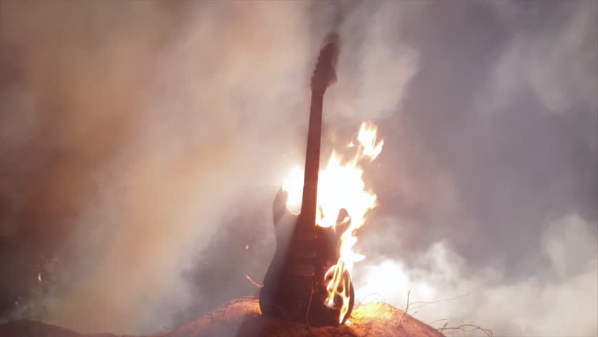 Electric rock guitar set on fire. Burning in slow motion. Authentic creative shot.