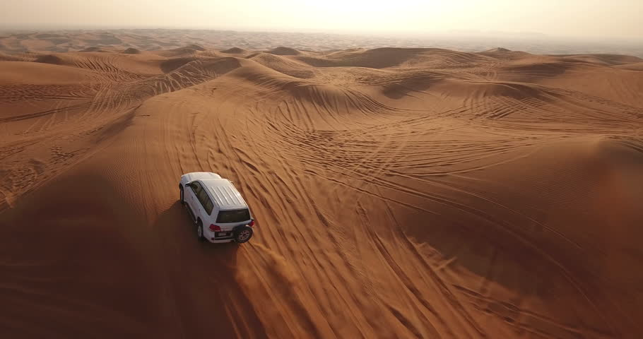 DUBAI, UAE - JANUARY 3, 2017: Aerial view of jeep driving in desert at sunrise. A desert safari is peculiar to Dubai and the UAE. A trip that lasts a couple of hours as you move through the sand dunes