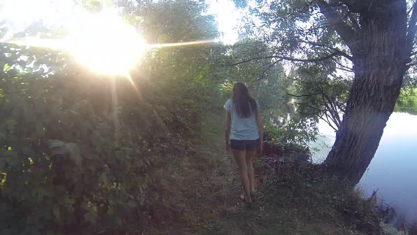 Rear back view of young female hiker walking on trek through rain forest near river.  | Shutterstock HD Video #23579818