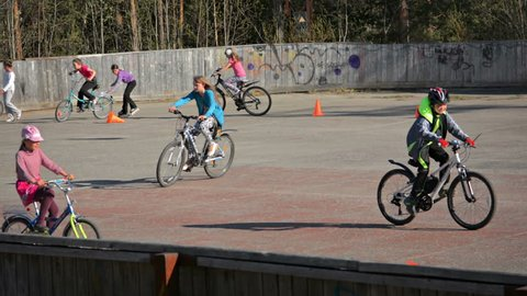 POLJARNIE ZORI. RUSSIA - CIRCA MAY 2015: Local Children Riding Bicycles at a Rural Park in Polyarnie Zori