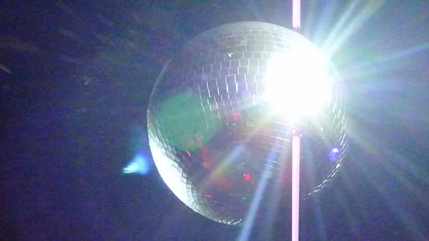 Nightclub disc ball spinning, reflecting light to zoom out - tilt down to people dancing blur. #2359109