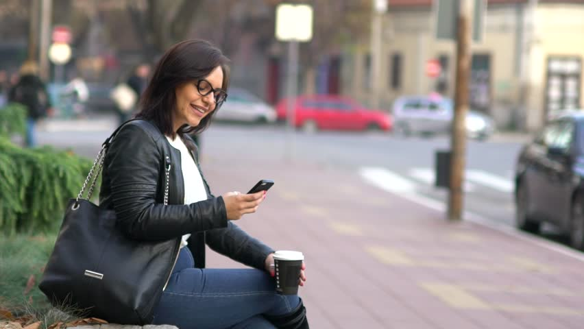 SLOW MOTION: Young Caucasian woman with coffee to go and smart phone downtown in urban surroundings. | Shutterstock HD Video #23610367