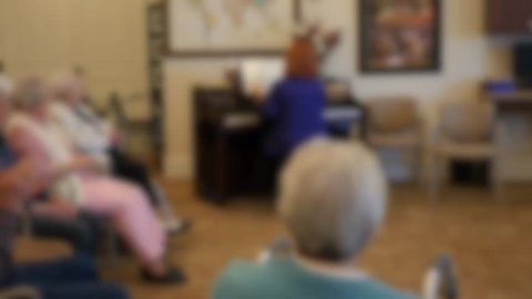 An out of focus shot of elderly people in an assisted living home listening to someone play the piano