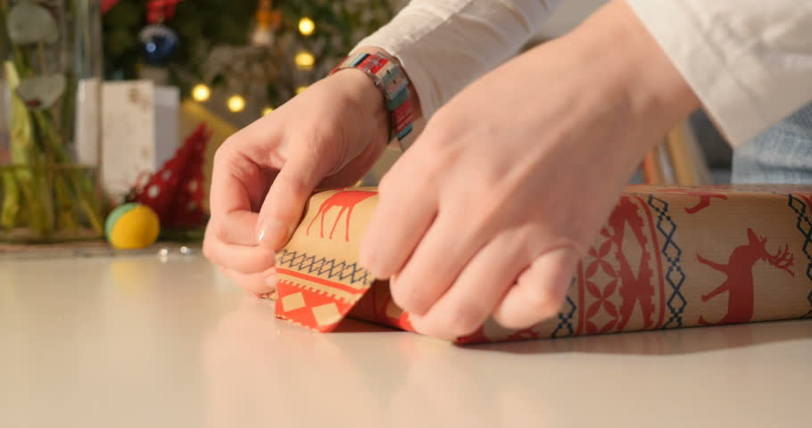Side view close-up of designer woman wrapping gift wrapped gift in festive paper for upcoming holiday, anniversary, wedding, Easter present Christmas gift and other needs | Shutterstock HD Video #23633287