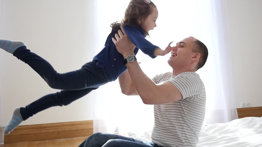 Happy Family Idyll Little Child Daughter Jump On Father Arms And They Fall On A Bed #23641642
