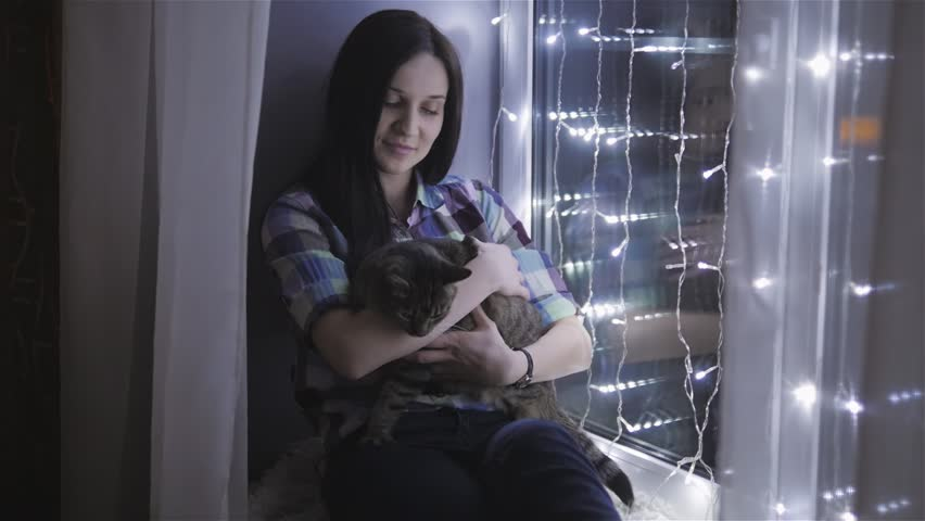 Beautiful Attractive Woman Stroking a Cat Sitting On Windowsill Decorated With Garlands | Shutterstock HD Video #23643262