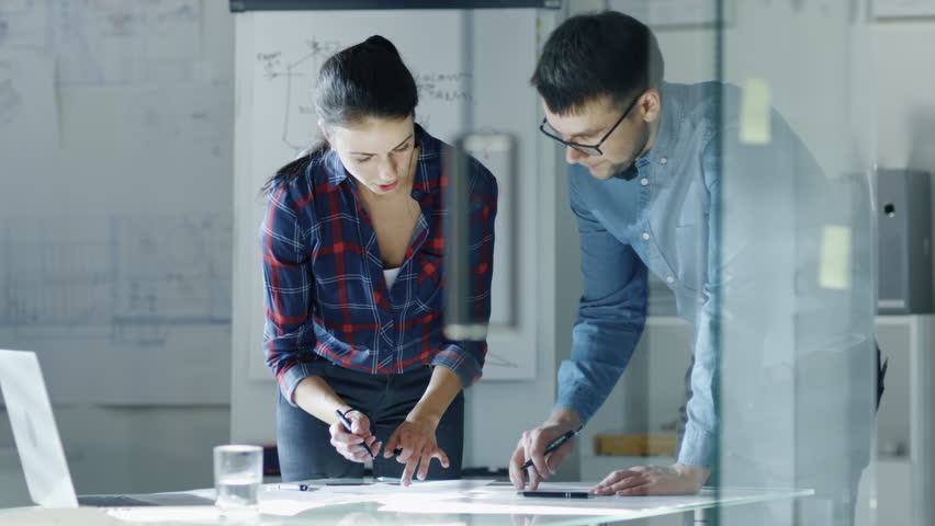 Male and Female Design Engineers Work on Drafts, Make Corrections and Discuss Their Project. On the Background Stands Whiteboard with Sketches. Shot on RED Cinema Camera 4K (UHD).