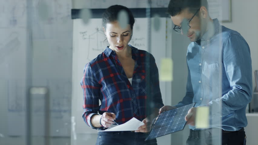 Late at Night Male and Female Solar Engineers Discuss Drafts and Part of a Solar Panel. Woman Holds Drafts, Man Hold Panel. In the Background Whiteboard with Sketches, Pinned to the Wall Blueprints.  | Shutterstock HD Video #23651740