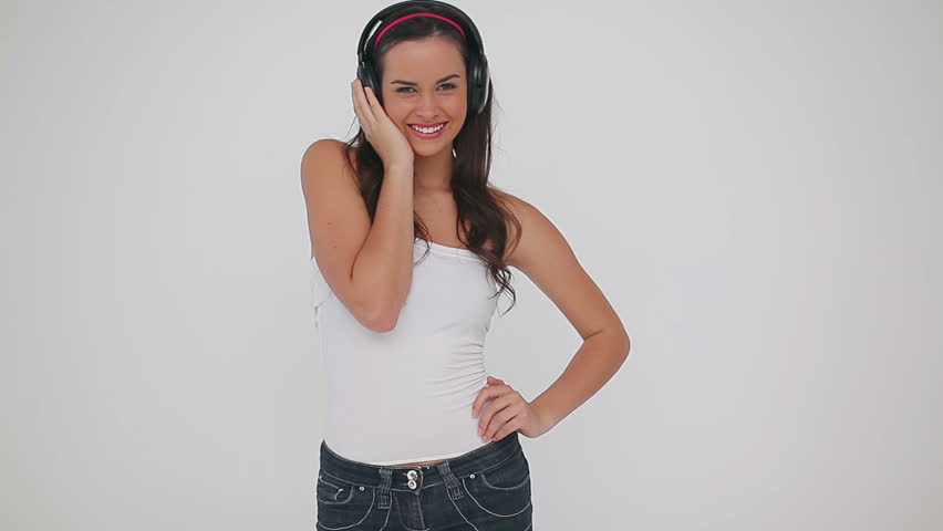 Smiling brunette listening to music on headphones against a grey background   Shutterstock HD Video #2365700