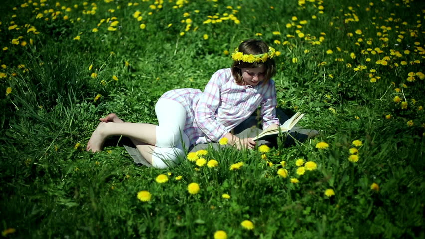 Teenager girl lying on meadow full of sow-thistle and reading book