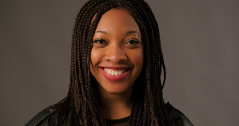 Happy smiling African young woman close up portrait with braids against dark background.