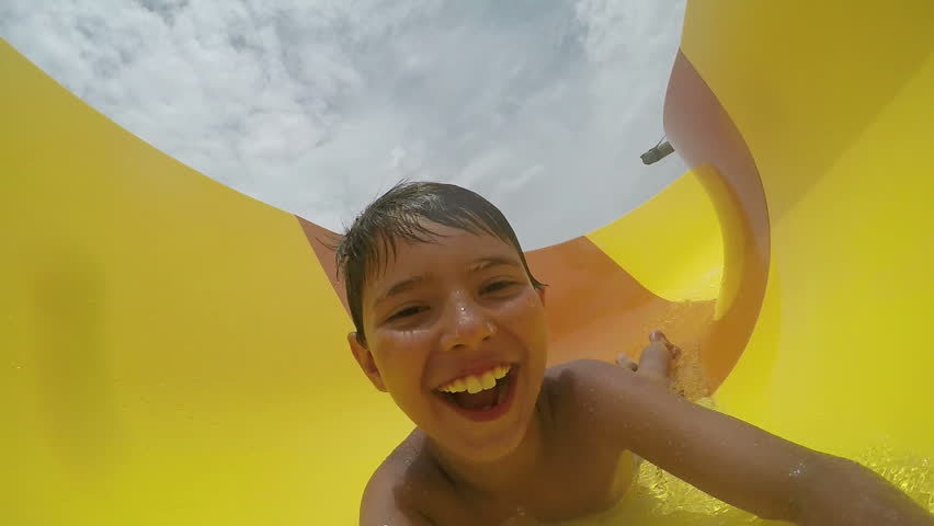 Little funny boy rolls a water slide at a water park