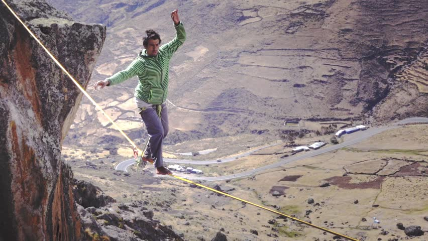 Slack liner balancing on tightrope between two rocks, Snowy mountains of the Huascaran park on the background, Peru. Slow motion