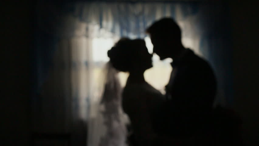 Silhouettes of the bride and groom. Kiss in the dark before the celebration. | Shutterstock HD Video #23725555