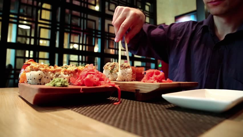 Man sits at the table in restaurant and eats japanese food. Boy in purple shirt eats sushi in japanese restaurant | Shutterstock HD Video #23737927