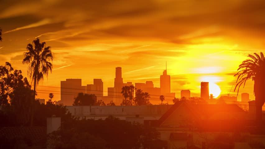 Fiery sunrise over city of Los Angeles downtown skyline. 4K UHD Timelapse.