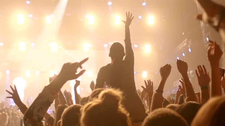girl at a concert seating on shoulders & raising her hands. #23749477