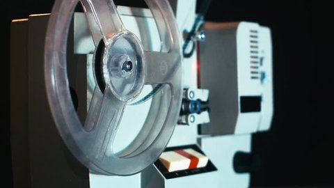 Old film camera projection is started by hand by a man, then stops it after a while 14