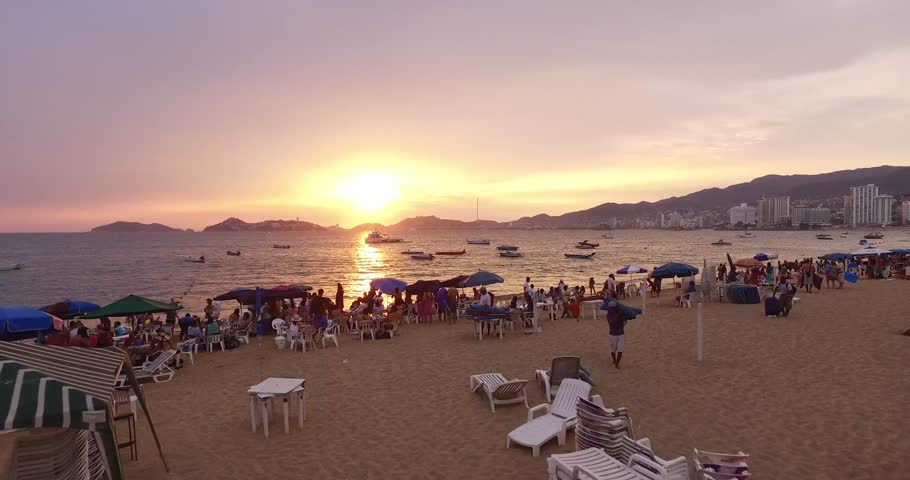 4K aerial of a busy beach in Acapulco flying over the ocean during a beautiful sunset