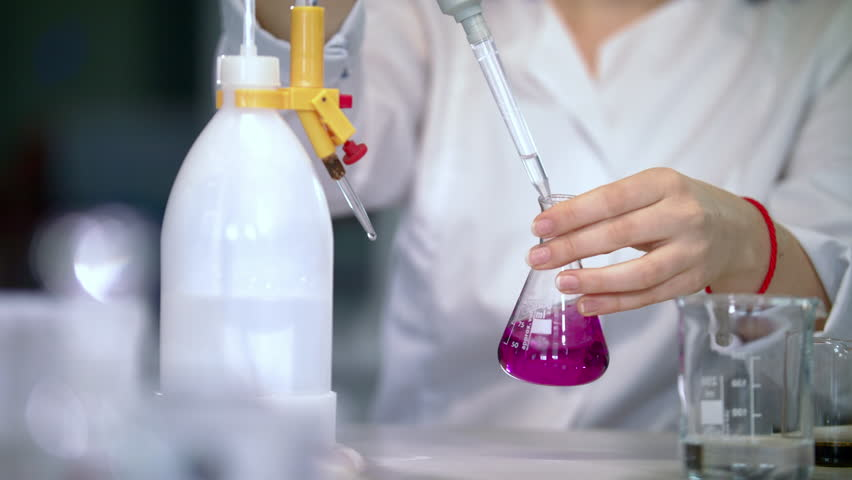 Scientist working with chemical reaction in chemistry lab. Chemical reaction in glass flask. Lab worker doing chemical experiment in laboratory