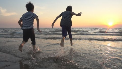 Little boy playing at the beach sunset slow motion HD