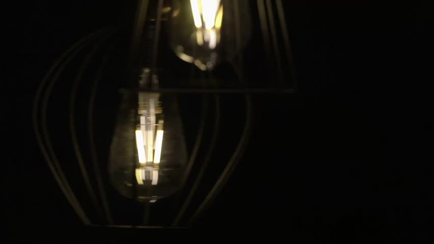 Bulb moves on a wire (naturally). Lamp swinging on a black background. Slow motion. | Shutterstock HD Video #23783473